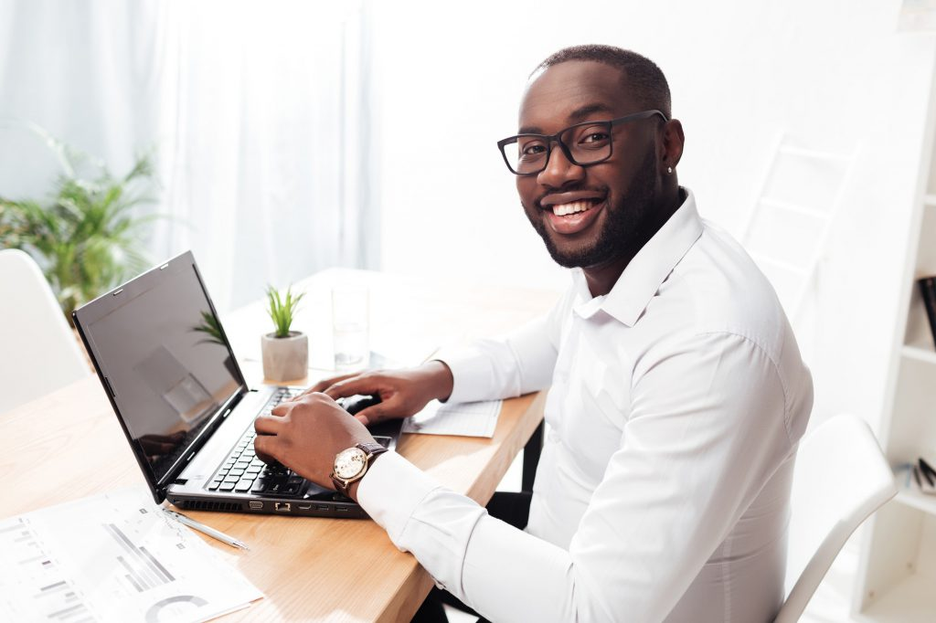 Cheerful African American businessman happily looking in camera working on his laptop in office